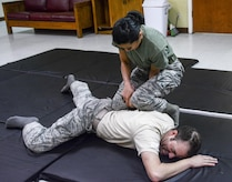 U.S. Air Force Capt.  Elizabeth Guidara , 315th Training Squadron student, demonstrates combative techniques on U.S. Air Force Capt. Justin Arbogast, 315th Training Squadron student, during her course at the local women's shelter San Angelo, TX, Oct 21, 2017. Guidara initiated the program to teach women skills and techniques against physical intimidation.