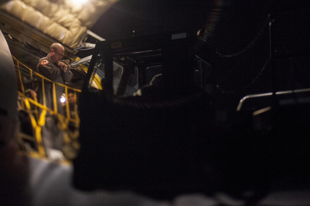 A U.S. Air Force Airman guides a 60K aircraft cargo loader while unloading gear from a KC-135 Stratotanker at Joint Base McGuire-Dix-Lakehurst, N.J., Nov. 21, 2017. This photo was taken with a tilt-shift lens. (U.S. Air National Guard photo by Master Sgt. Matt Hecht)