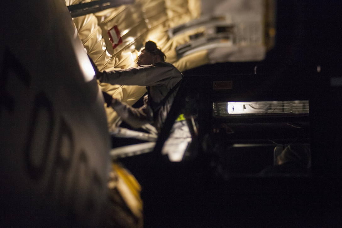 A U.S. Air Force Airman with the 305th Air Mobility Wing talks to aircrew while unloading gear from a 108th Wing KC-135 Stratotanker at Joint Base McGuire-Dix-Lakehurst, N.J., Nov. 21, 2017. This photo was taken with a tilt-shift lens. (U.S. Air National Guard photo by Master Sgt. Matt Hecht)