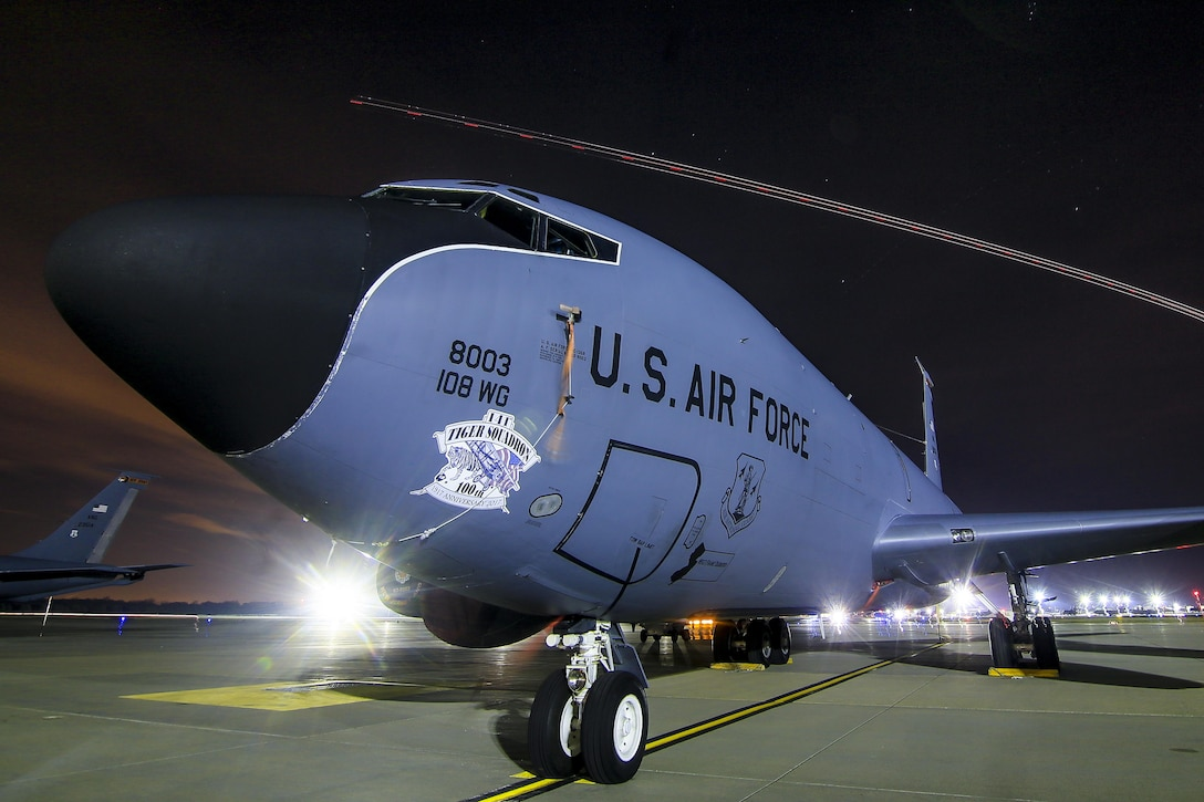 A New Jersey National Guard KC-135R Stratotanker from the 108th Wing sits on the flightline on Joint Base McGuire-Dix-Lakehurst, N.J, Nov. 21, 2017. The light trail from a C-17 Globemaster III can be seen in the distance. This photo was captured with a 30 second exposure. (U.S. Air National Guard photo by Master Sgt. Matt Hecht)