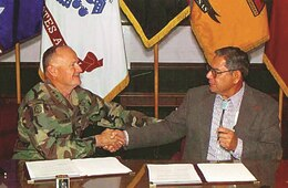 Representatives from Fort Riley and one of the 12 Native American tribes that works with the installation shake hands over an agreement solidifying the relationship between post and the tribe in April 2000.