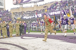 Staff Sgt. John Hylander, 2nd Battalion, 70th Armor Regiment, 2nd Armored Brigade Combat Team, 1st Infantry Division, leads the Kansas State University football team onto the field at Bill Snyder Family Stadium Nov. 11 as part of Fort Riley Day at K-State. Hylander was selected to lead the team because he is the Noncommissioned Officer of the Year for 1st Inf. Div.