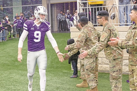 Mitch Lochbihler, 9, greets 1st Infantry Division Soldiers before the game on Fort Riley Day at Bill Snyder Family Stadium on the Kansas State University campus Nov. 11.