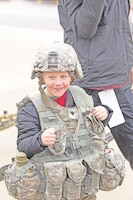 Dane Sheldon of Wamego, Kansas, tries on the body armor and other military gear from a 1st Infantry Division Soldier outside of Bill Snyder Family Stadium during Fort Riley Day at Kansas State University Nov. 11.