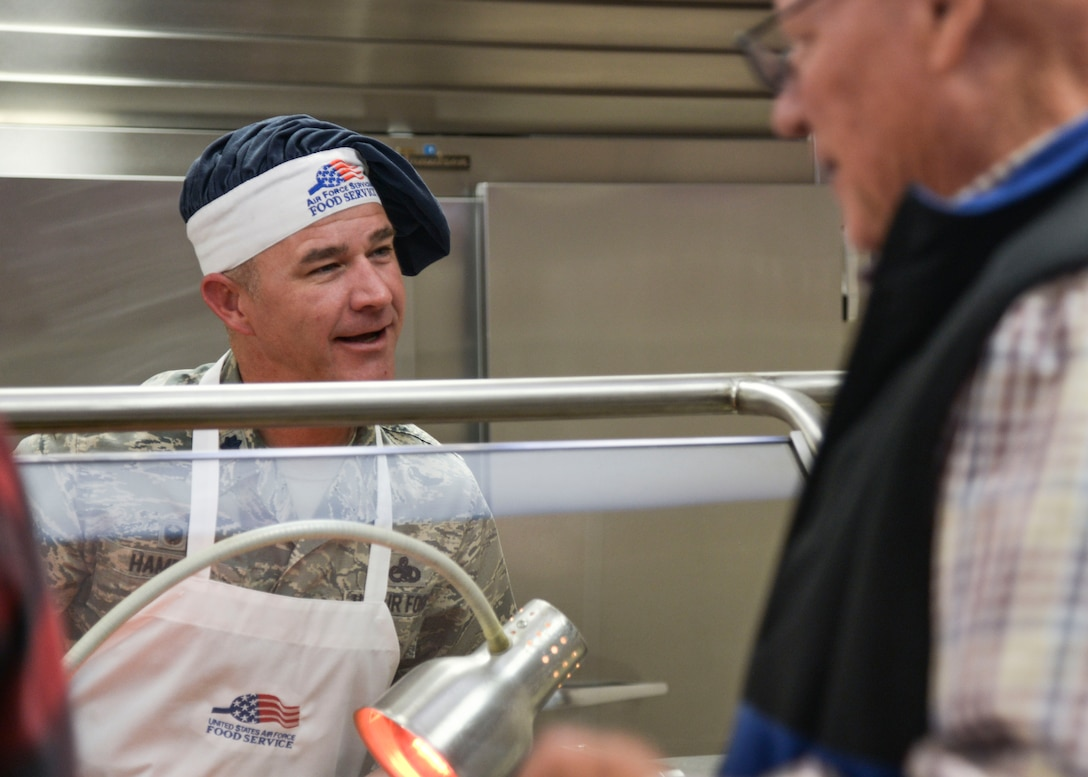 Lt. Col. John Hampel, 898th Munitions Squadron commander, serves holiday meals at the Thunderbird Inn Nov. 24. Several commanders and command chiefs took a shift serving meals at the dining facility on Thanksgiving to show their appreciation to all Airmen, retirees, and their families.