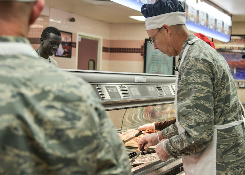 Col. Richard Gibbs, 377th Air Base Wing commander, serves a Thanksgiving meal to an Airman Nov. 24. Several commanders and command chiefs took a shift serving meals at the dining facility on Thanksgiving to show their appreciation to all Airmen, retirees, and their families.