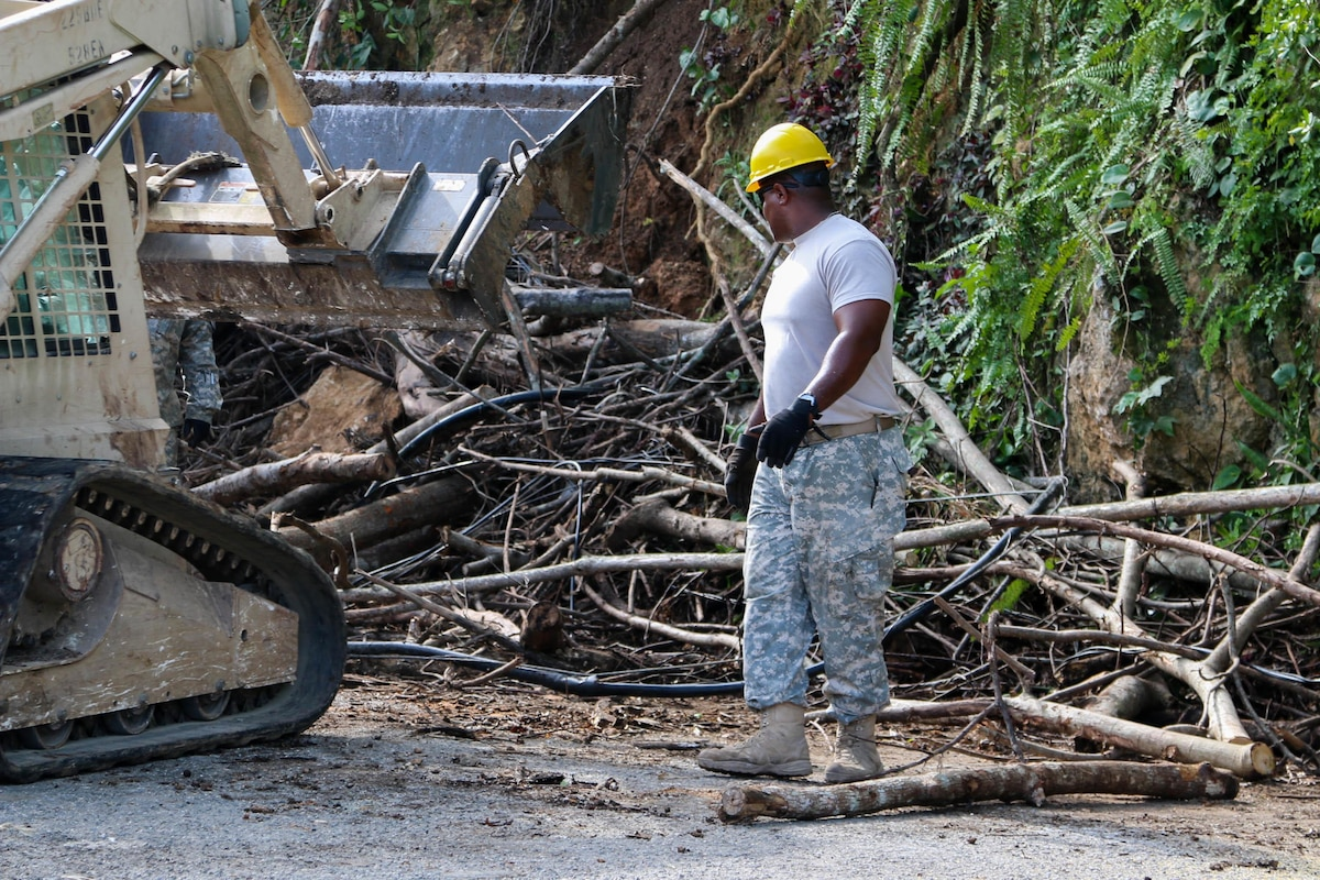 A National Guard soldier works in the clearance of a road.