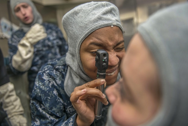A sailor practices using an ophthalmoscope to examine eyes.