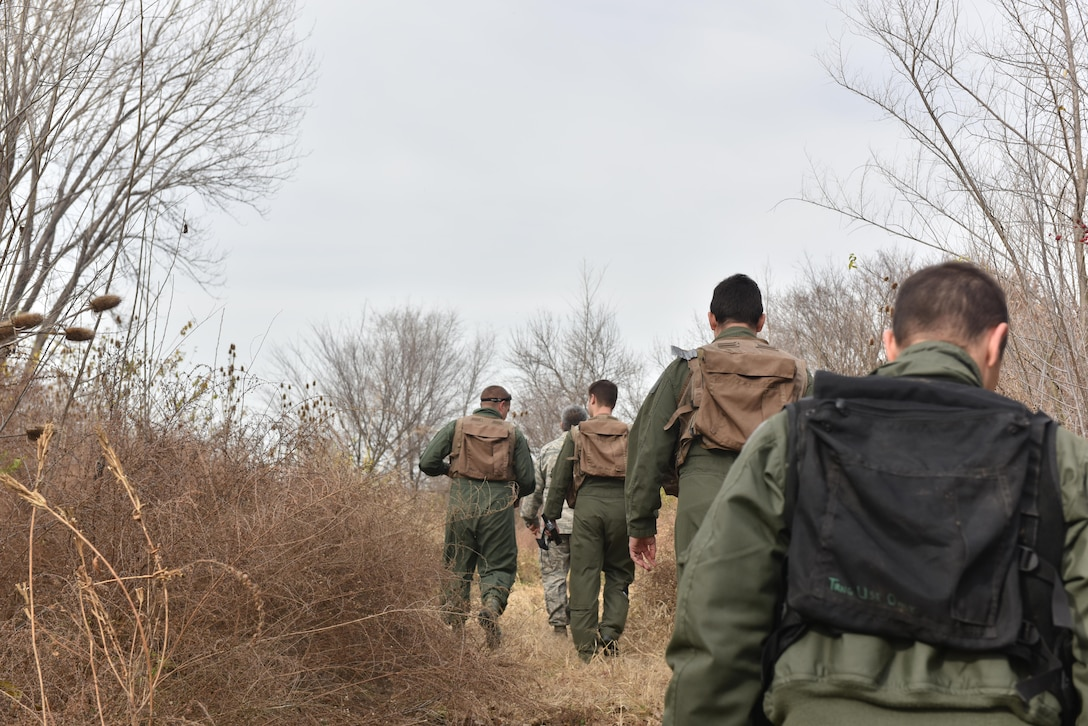 US Air Force Tech. Sgt. Sergio Avalos, a survival, evasion, resist and escape (SERE) specialist, trek through bushes with pilots of Team Whiteman to a designated starting area to conduct the navigation portion of their SERE training Nov.27, 2017 at Whiteman Air Force Base, Missouri. During this portion the pilots are must use given coordinates to locate a meeting point with the SERE instructor.