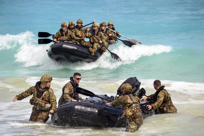 Soldiers make a beach landing with combat rubber raiding craft.