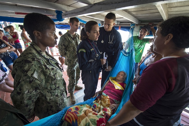 Navy specialists work to diagnose a woman on her houseboat.