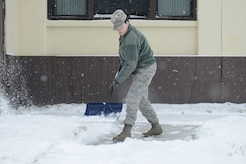 An Airman shovels a walkway at Joint Base Elmendorf-Richardson, Alaska, March 4, 2016. Airmen, Soldiers and their families who reside in JBER's Aurora Military Housing are responsible for removing snow and ice from driveways and sidewalks within 24 hours of snowfall.