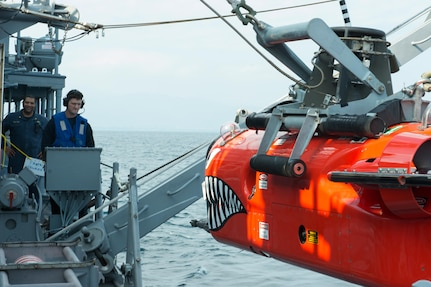 Mineman 1st Class Justin Crabtree, from Diamondhead, Miss., lowers a mine neutralization vehicle aboard the Avenger-class mine countermeasures ship USS Chief (MCM 14) into the water to track mines and simulate delivering an explosive package.