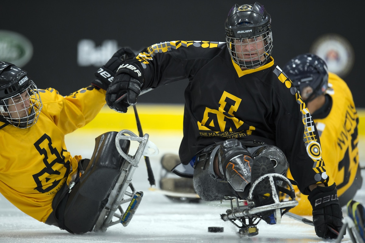 Two wounded warriors play hockey on an ice rink.