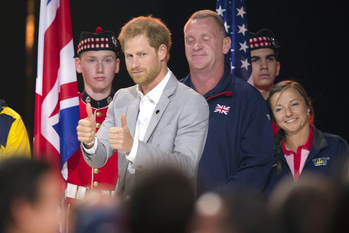 Prince Harry gives two thumbs up while surrounded by other people.