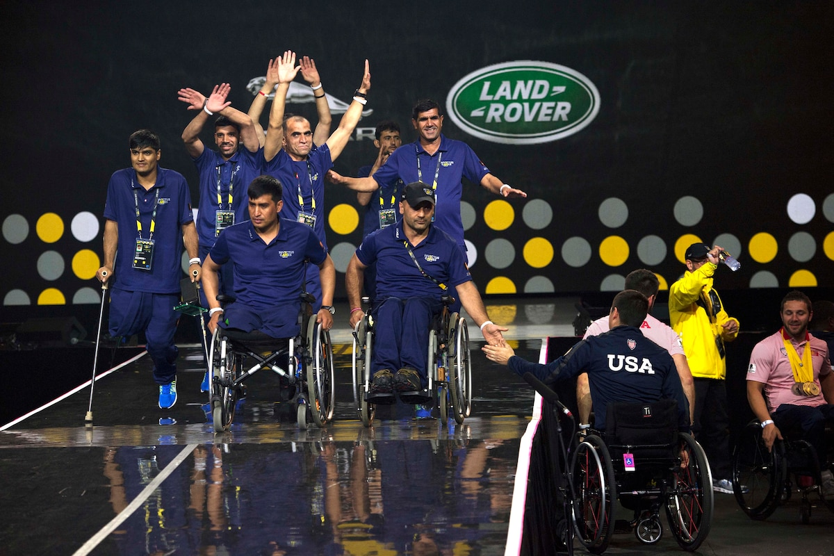 A group of people on stage is high-fived by a person in a wheelchair off stage.