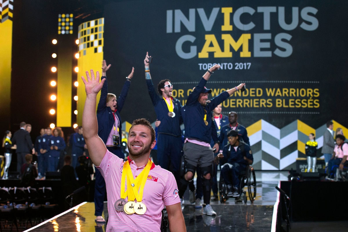 A member of Team U.S. waves onstage a group of people behind him.