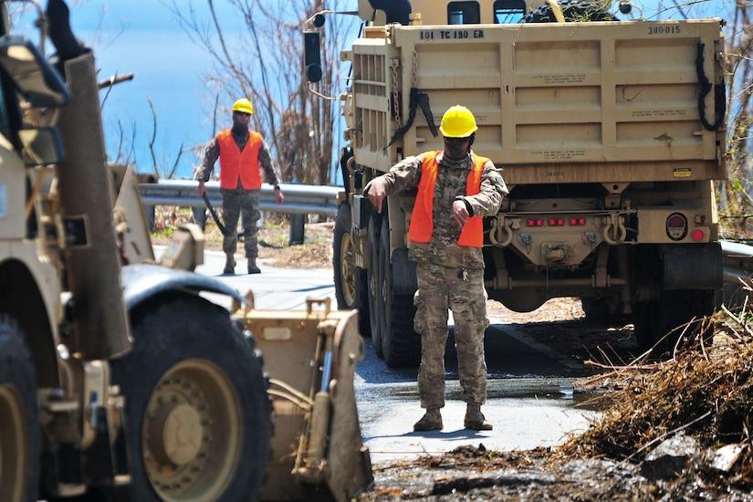 A Guardsman guides a bulldozer to remove debris from a road.