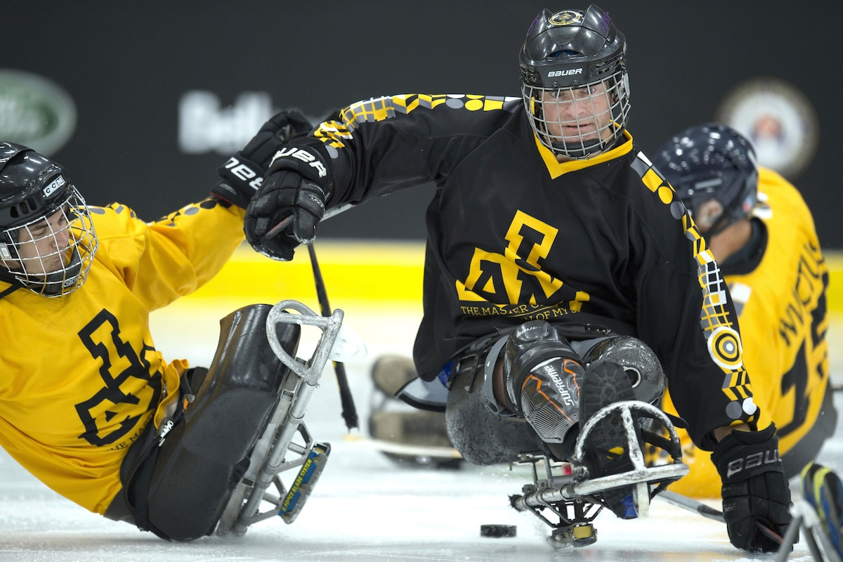 A sledge hockey player pushes another sledge hockey player.