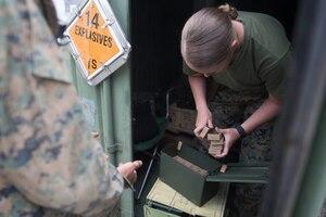 A female marine counts ammunition.