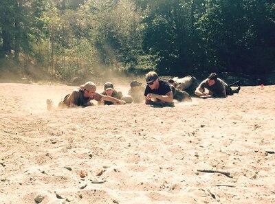 Service members crawl on desert terrain.