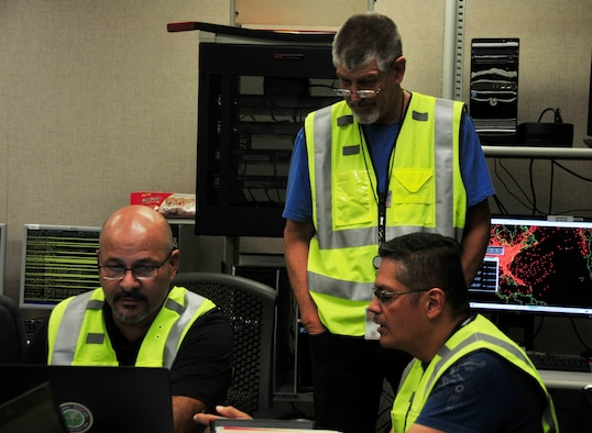Operations manager Edward Tirado (right) communicates with members of the emergency operations center team at the FAA's Puerto Rico Operations Center, Sept. 30, 2017. The partnership between the FAA and the Puerto Rico Air National Guard was instrumental in restoring air traffic operations.  (U.S. Air National Guard Photo by Capt. Matt Murphy)