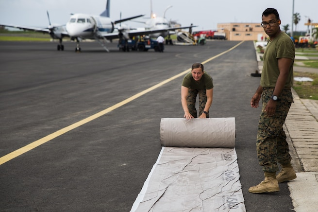 U.S. Marines with Joint Task Force - Leeward Islands unroll a tarp as they prepare supplies for distribution in Dominica