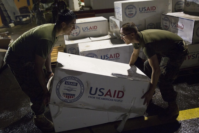 U.S. Marines stack boxes of tarps as they prepare supplies for distribution in Dominica.