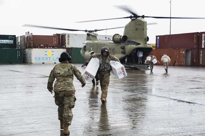 U.S. service members unload supplies from a U.S. Army helicopter in Dominica.