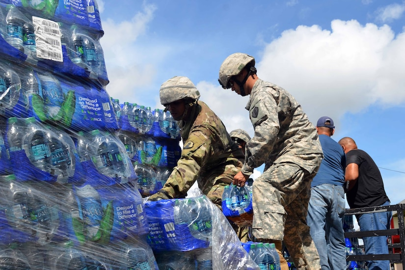 Soldiers load cases of bottled water onto a truck.