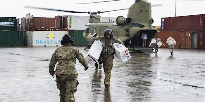 U.S. service members unload supplies from a helicopter in Dominica.