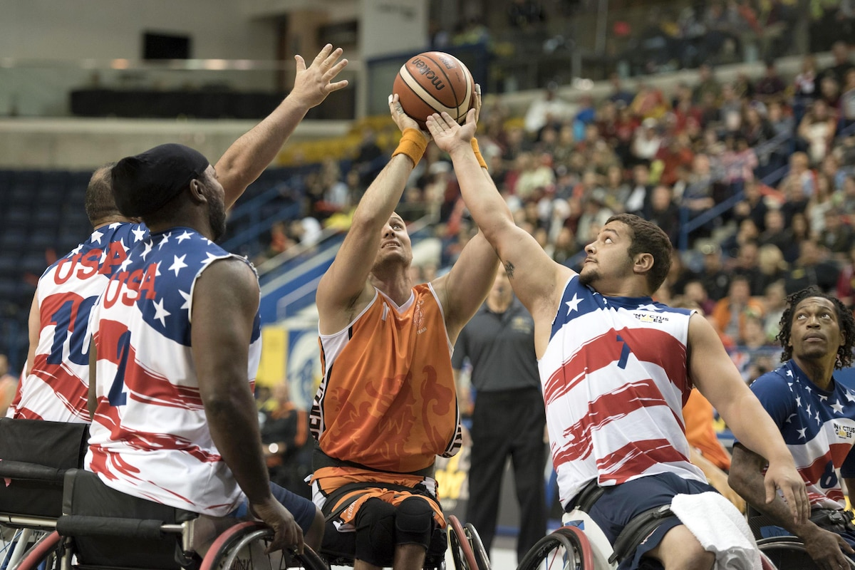 Four athletes in wheelchairs reach up for a basketball.