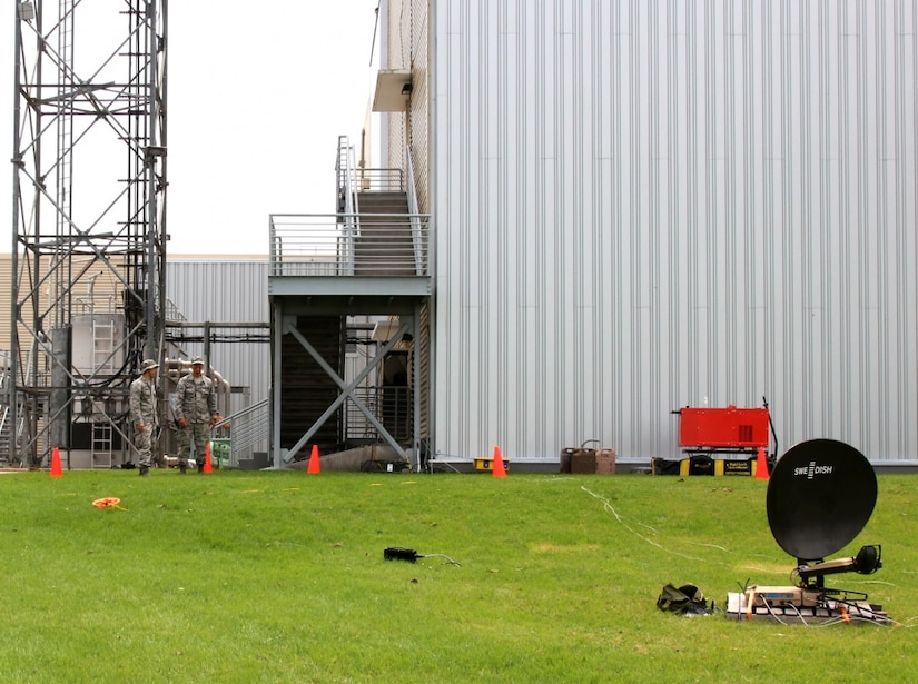 Airmen look at a satellite dish.