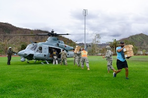 Service members unload supplies from a military helicopter.