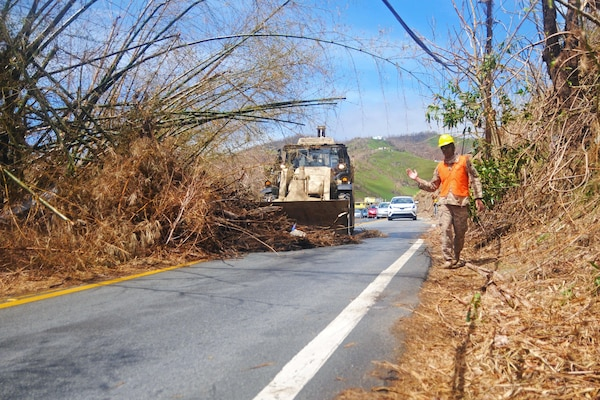 A Guardsman guides a bulldozer to clear debris and trees from roads.