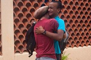 Two men embrace in a hug.