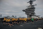 Chief selects run in formation during an Applied Suicide Intervention Skills Training 5k run on the flight deck of the aircraft carrier USS Theodore Roosevelt