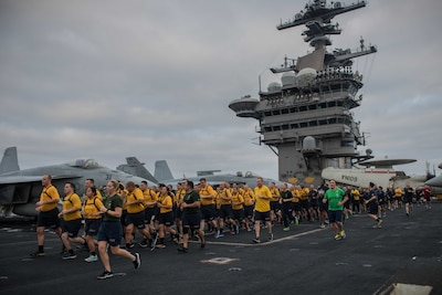 PACIFIC OCEAN (Aug. 17, 2017) Chief selects run in formation during an Applied Suicide Intervention Skills Training (ASIST) 5k run on the flight deck of the aircraft carrier USS Theodore Roosevelt (CVN 71). Theodore Roosevelt is underway conducting a composite training unit exercise (COMPTUEX) with its carrier strike group in preparation for an upcoming deployment. COMPTUEX tests a carrier strike group's mission readiness and ability to perform as an integrated unit through simulated real-world scenarios. (U.S. Navy photo by Mass Communication Specialist 3rd Class Alex Perlman/Released)
