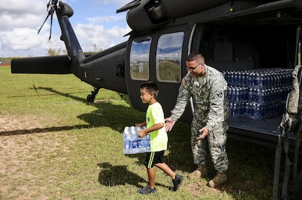 A soldier watches a child carrying a case of water away from a helicopter.