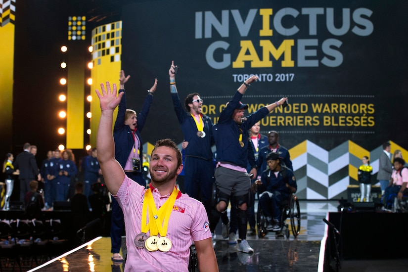 Navy Petty Officer 3rd Class Nathan Dewalt waves as Team U.S. enters the 2017 Invictus Games closing ceremony.