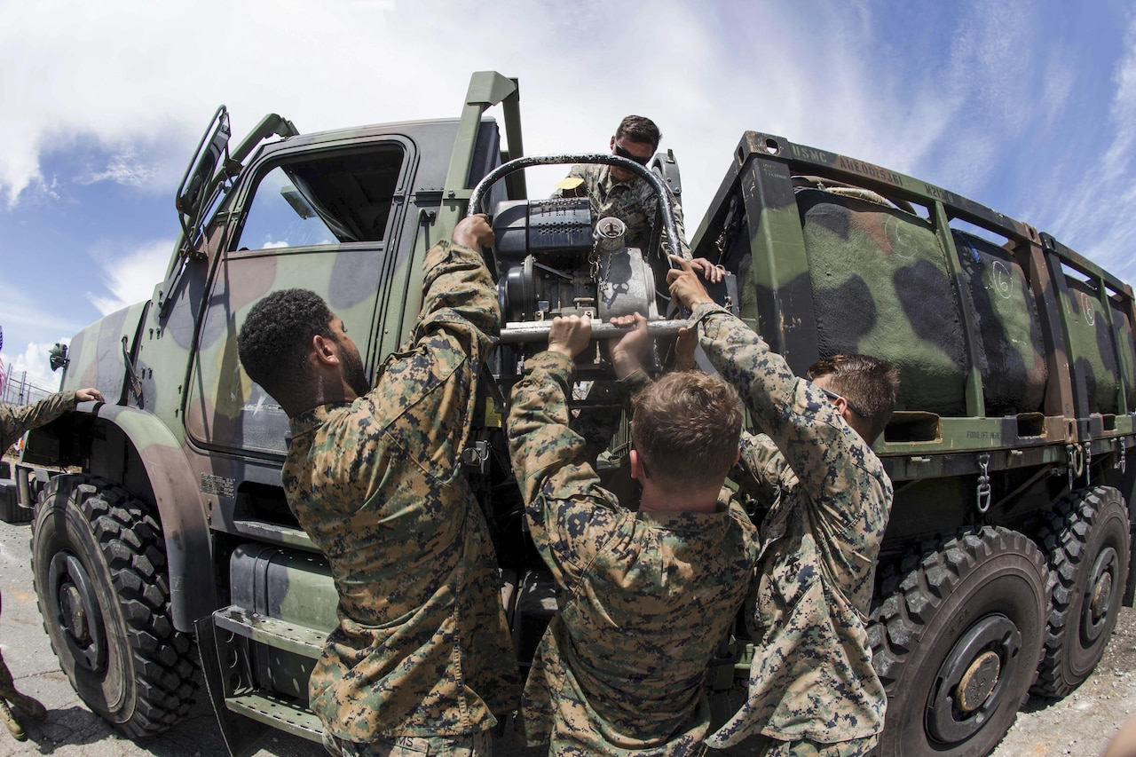 Marines lower a water pump from a vehicle.