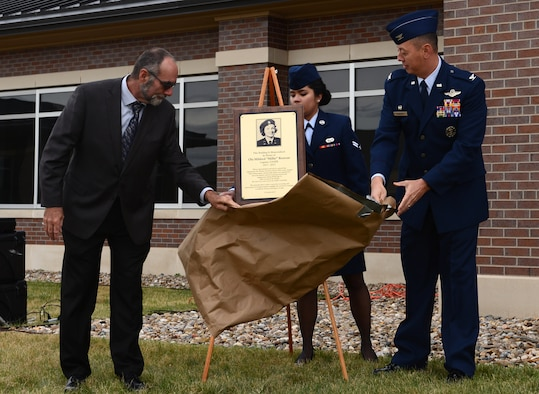 "Forest R. McDonald, son of Ola ""Millie"" Rexroat, and Col. John Edwards, commander of the 28th Bomb Wing, unveil the plaque honoring Rexroat during a building dedication at Ellsworth Air Force Base, Oct. 2, 2017. While serving as a WASP, Rexroat towed targets behind a T-6 Texan for air-to-air gunnery and ground-to-air anti-aircraft practice for male pilots. She also transported personnel and cargo. After the WASPS disbanded, Rexroat served another ten years in the Air Force Reserves as an air traffic controller. (U.S. Air Force Photo by Airman 1st Class Donald C. Knechtel)"