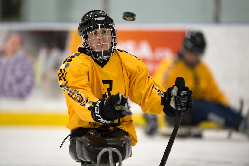 Marine Corps Sgt. Ivan Sears flips a puck during practice for a 2017 Invictus Games sledge hockey game.
