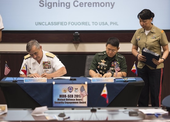 CAMP H.M. SMITH, Hawaii (Sept. 28, 2018) — Adm. Harry Harris, Commander of U.S. Pacific Command (PACOM), and Gen. Eduardo Año, Chief of Staff for the Armed Forces of the Philippines, sign paperwork for the Mutual Defense Board (MDB) and Security Engagement Board (SEB). During Año's two-day visit to PACOM, he and Harris discussed changes to the MDB and SEB. The MDB provides direct liaison and consultation on military matters of mutual concern to develop and improve both countries' common defense. The SEB provides the framework and mechanism for continuing liaison and consultation on non-traditional threats to security such as terrorism, transnational crimes, maritime security, and natural and man-made disasters. (U.S. Navy photo by Mass Communication Specialist 2nd Class James Mullen/Released)