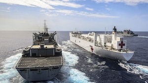 Three ships travel in the ocean.