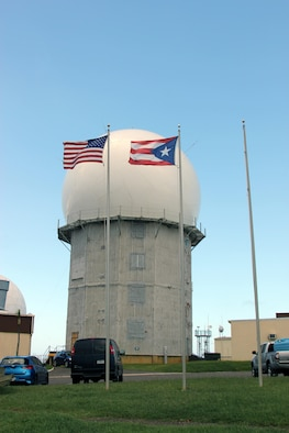The U.S. and Puerto Rico flags flap in a stiff breeze in front of the radar tower operated by 140th Air Defense Support Squadron in Aguadilla,