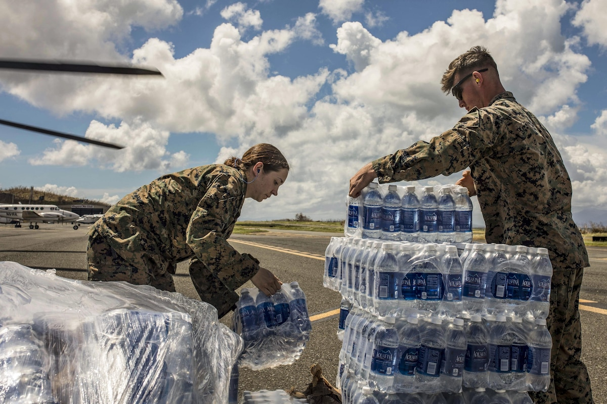 Two Marines unload and stack cases of water