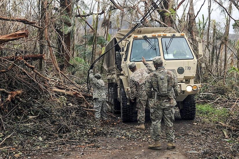 Soldiers clear debris along a roadway.