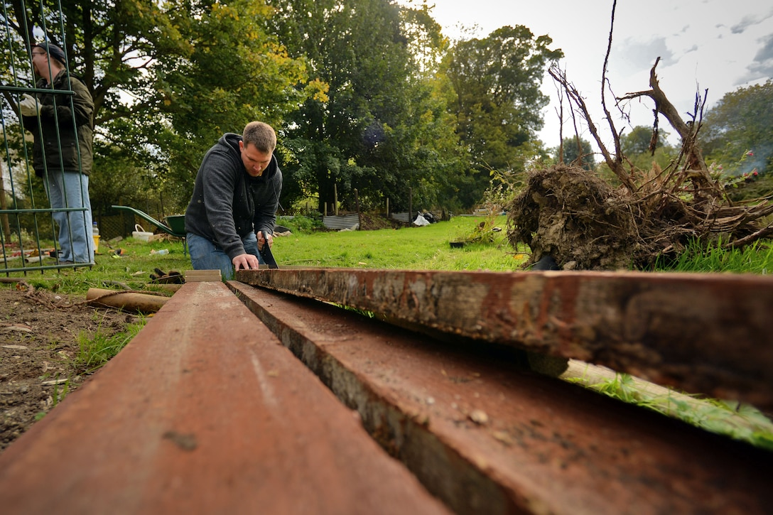 U.S. Air Force Tech. Sgt. Christopher Moore, 488th Intelligence Squadron NCO in charge of information assurance, cuts planks of wood in preparation for building a dock Oct. 2, 2017, at Middlefield Manor in Barton Mills, England. Airmen from the RAF Mildenhall Team 5/6 volunteered their time helping the residents by chopping wood, building a boat landing dock, putting up a fence and cutting reeds within the river. (U.S. Air Force photo by Senior Airman Christine Groening)