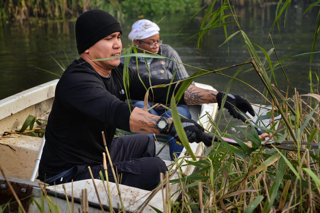 U.S. Air Force Tech. Sgt. Christian Bennet, 352nd Special Operations Wing NCO in charge of personnel programs, cuts reeds in the River Lark Oct. 2, 2017, at Middlefield Manor in Barton Mills, England. Members from the RAF Mildenhall Team 5/6 worked with the residents at Middlefield Manor, providing assistance with any yard work they may need help with. Middlefield Manor is a care home for residents who are autistic. (U.S. Air Force photo by Senior Airman Christine Groening)